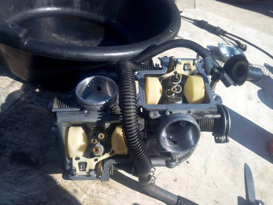 Here are the carburetors in the process of being cleaned up, really bad gas in the fuel tank which looked rusty and smelled like varnish, was also in the carburetors, dirty and clogged with the old fuel, bowls, needles, seats, main, and pilot jets all needed a major cleaning on this 2003 750 Honda Shadow Ace Cruiser. The customer called PMC Super Tuners out for no start diagnostics, this is when the technician found the tires low, battery dead. The throttle cables were stuck, the oil, and spark plugs, needed changing too.